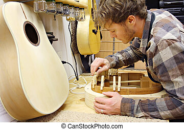 Woodworker Building Guitar in Workshop - a young man who is...