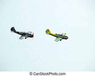 Group aerobatics - Two small propeller planes performing...