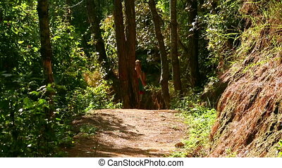 Sexy girl running along narrow footpath in forest