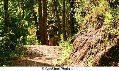 Tourist couple running along narrow footpath at Nagarkot,...