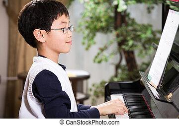 Playing piano - A shot of an asian boy playing piano