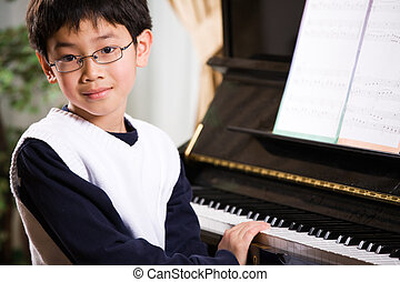 Playing piano - A shot of an asian boy playing piano