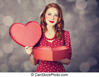 Redhead girl with gift for Valentines Day. Photo with bokeh...