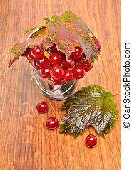 Red viburnum berries in the glass on the wooden background