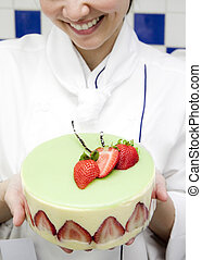 Woman chef holding strawberry cake