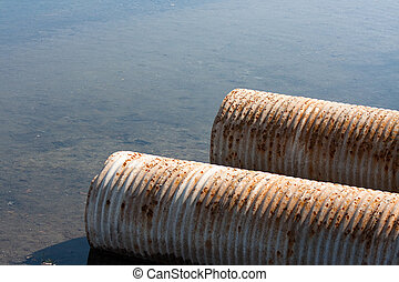 Rusty drainage pipes emptying into a river