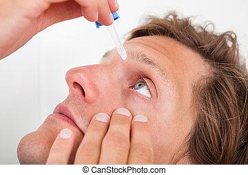 Young Man Putting Eye Drops