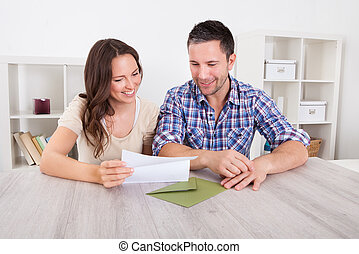 Happy Couple Reading Paper - Portrait Of A Happy Young...