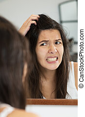 Woman having a bad hair day grimacing in disgust as she...