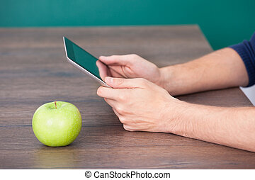 Person Using Digital Tablet Besides Green Apple - Close-up...