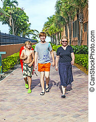 mother with two sons on the way to the beach with beach...
