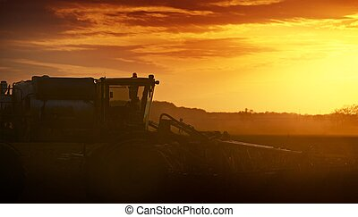 Cultivating in Sunset. Tractor Works on the Field....
