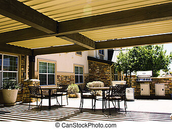 Covered hotel patio with tables and barbeque in summer light