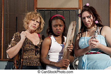 Three rough women on a house step
