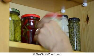 pickled vegetable jars - hand takes three small jars of...