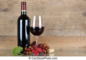 Red wine in wine bottle and glass in front of a wooden...