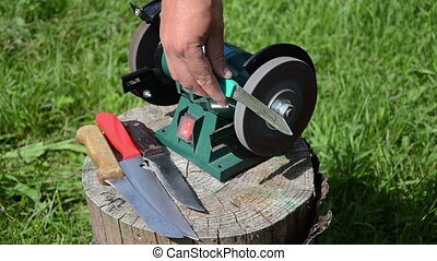 whestone blade - man sharpening with electric whetstone...