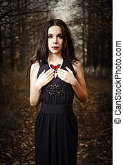 Beautiful girl holds red butterfly in hands. Outdoor...