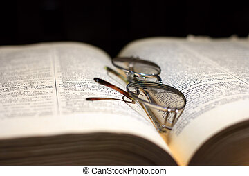 education - old book and glasses for the correction of sight