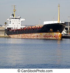 Merchant ship berthed at the harbour in a sunny day