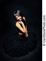 young brunette woman in a long black dress on a black...