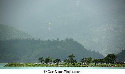 Paragliding over Pokhara Lake, Nepal - Paraglides in the sky...