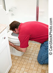 Man Vomiting in Toilet - Man kneeling down in the bathroom,...
