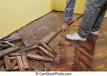 Home renovation - Worker demolishing oak parquet with...