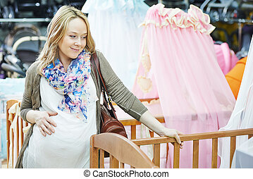 Young pregnant woman choosing cot or bassinet for newborn...