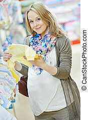 Young pregnant woman at clothes shop - Young pregnant woman...