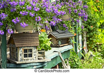 Beautiful Garden with Wood Bird Houses and Blossom Flowers....