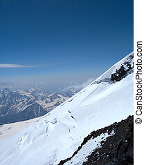 mountainside - snowy mountainside with blue sky in the...