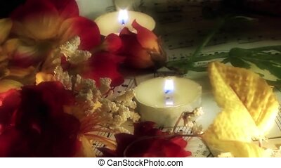 Music sheets and flowers in candle