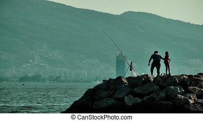 Fishermen and child silhouette on the rocks