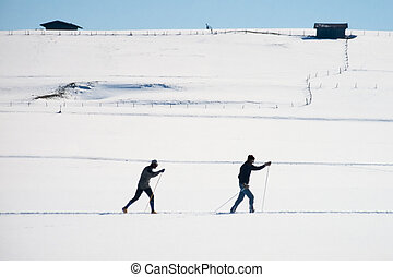 Cross country skiers skiing open expanse of snow - Two...