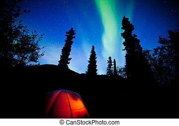 Orange taiga tent glow under northern lights flare - Tent...