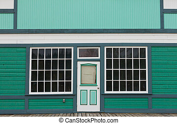 Small store front entrance to green wooden house -...