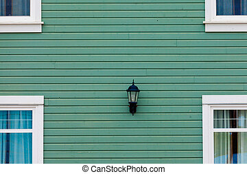 Exterior wall green siding center lamp and windows - Green...