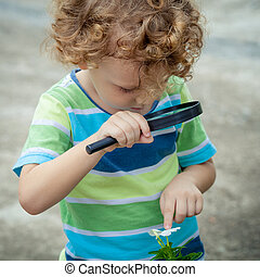 one little boy with magnifying glass outdoors in the day...