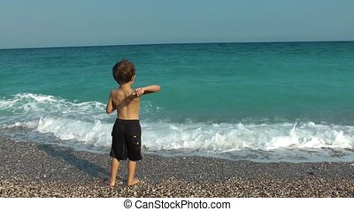 Boy Throwing stone to the sea