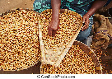 Peanuts - Woman with piles of peanuts on the street market...