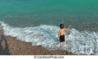 Boy throwing Stones to the Sea