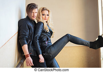 young embraced couple standing against wall