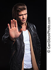 man in leather jacket making the stop hand gesture - young...