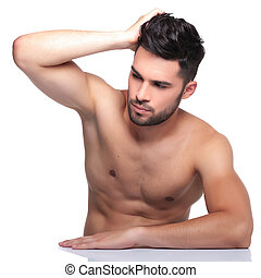 man passing his hand through his hair and looking away -...