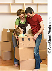 Happy family moving into a new home - Happy family of three...