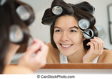 Woman in hair curlers applying eye makeup in the bathroom...