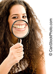 young woman holding magnifier and showing her magnified...