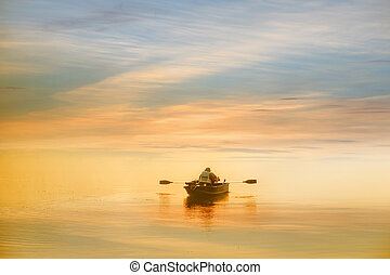 Boating in the dawn - Lonely man boating in the dawn