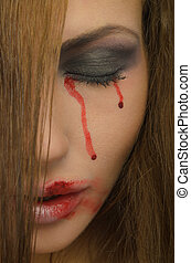 Blood from the eyes and face of woman close up